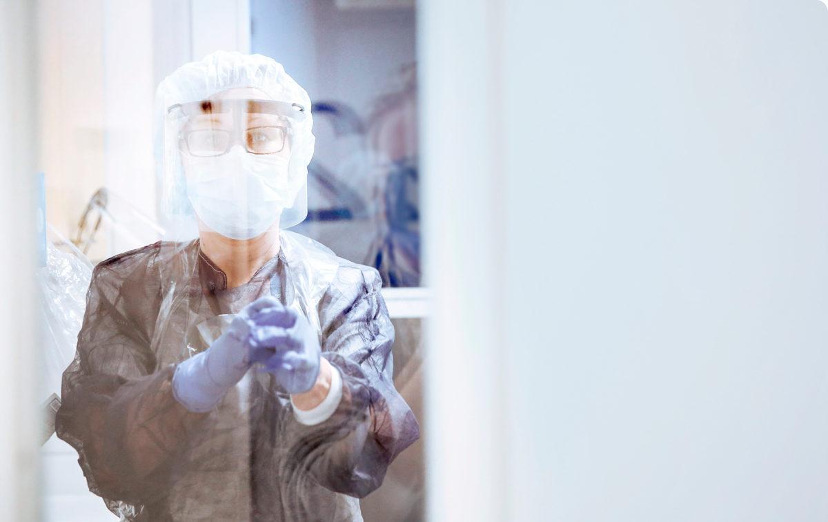 Valmiina taistoon. Apulaisosastonhoitaja Kaisa Haverinen pukee tarvittavat suojavarusteet ylle Malmin sairaalassa.