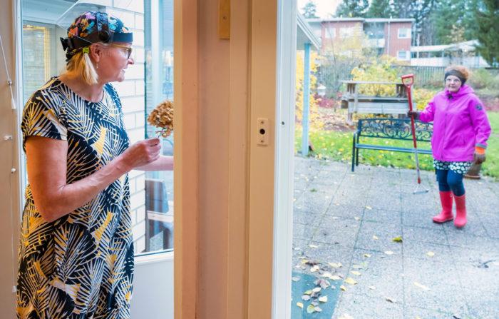 Marraskuun kukka. Tupahoivan yrittäjä Auli Härkälä on puutarhatöissä, kun Teija Riipinen miettii  sijoituspaikkaa saamalleen kukalle.